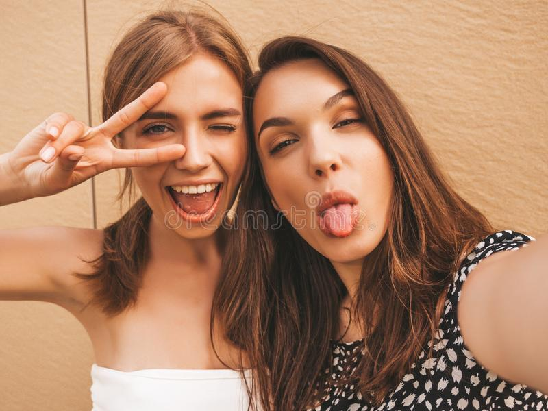 Two young beautiful smiling hipster girls in trendy summer clothes stock image