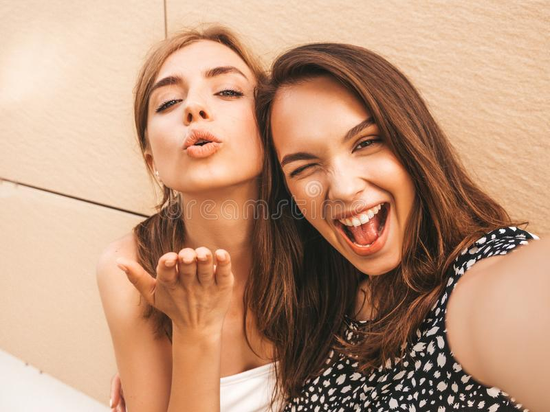 Two young beautiful smiling hipster girls in trendy summer clothes stock photography