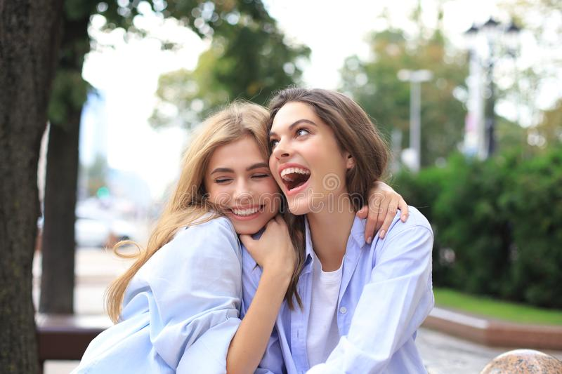 Two young smiling hipster women in summer clothes posing on street.Female showing positive face emotions royalty free stock images
