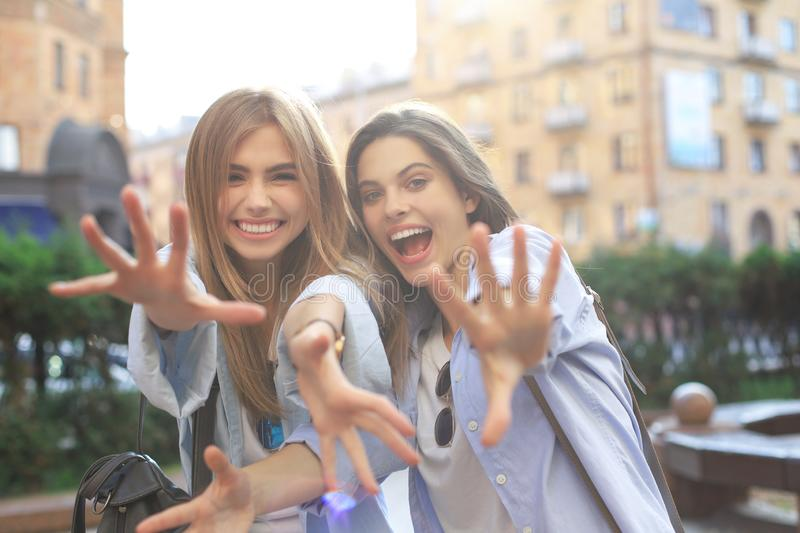 Two young smiling hipster women in summer clothes posing on street.Female showing positive face emotions stock photos