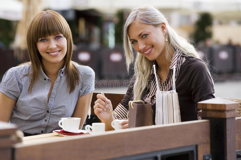 Two young smiling lady in cafe