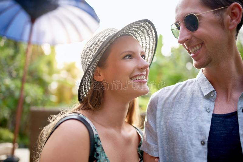 Two young smiling people wearing bright clothing in tropical loc. Bright portrait shot of happy millennial caucasian couple smiling at each other in sunlight stock photos