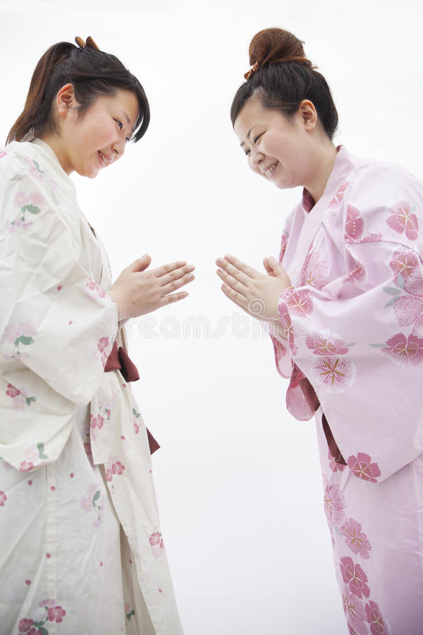 Two young smiling woman in Japanese kimonos bowing to each other, studio shot. Two young smiling women in Japanese kimonos bowing to each other, studio shot royalty free stock photography