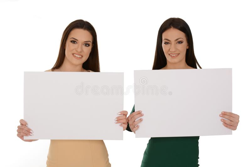 Two young smiling women holding two pieces of blank paper royalty free stock photos