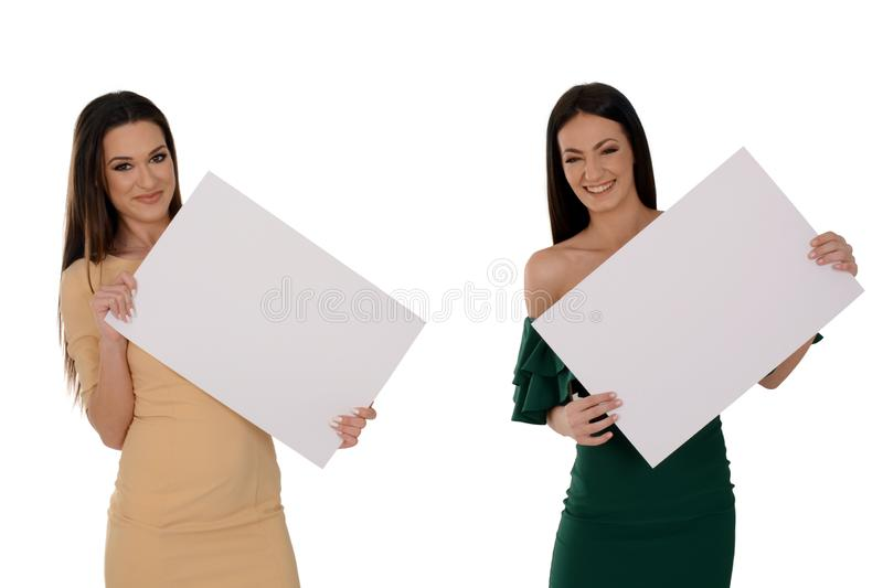 Two young smiling women holding two pieces of blank paper stock photos