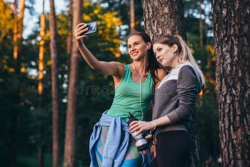 Two young sportive girlfriends wearing sportswear leaning against tree taking selfie with smartphone in forest stock image