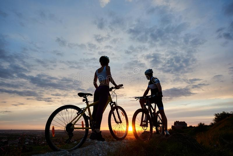Two young sports people on mountain bikes stand on rock at top of hill looking for sunset. Two young sports people on mountain bikes stand on rock on top of hill stock photos