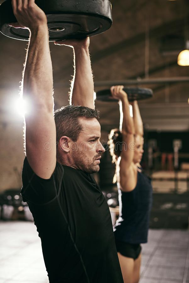 Two strong people working out in gym royalty free stock image