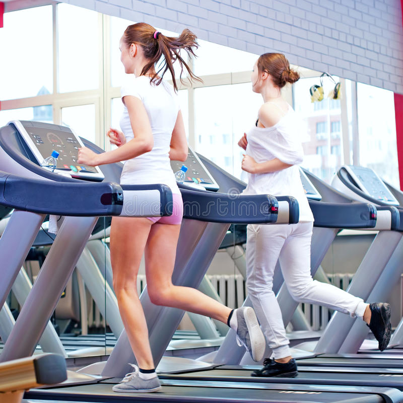 Two young sporty women run on machine royalty free stock photos
