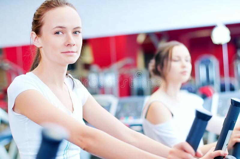 Two young sporty women run on machine royalty free stock photo