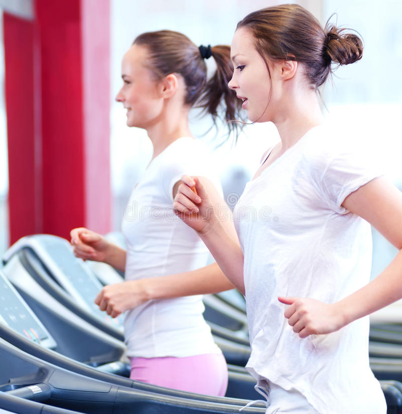 Two young sporty women run on machine royalty free stock image