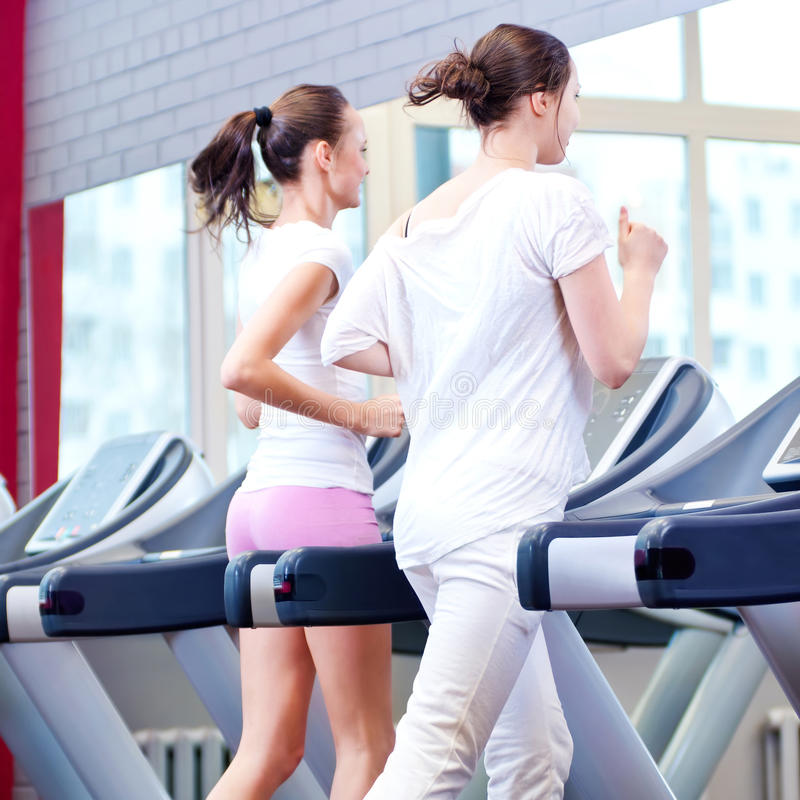 Two young sporty women run on machine royalty free stock images