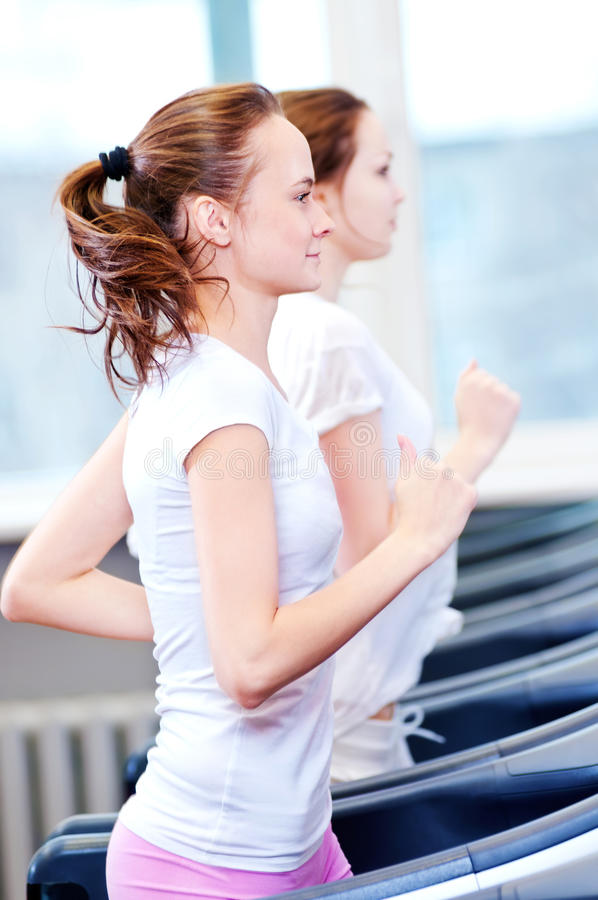 Two young sporty women run on machine stock photography