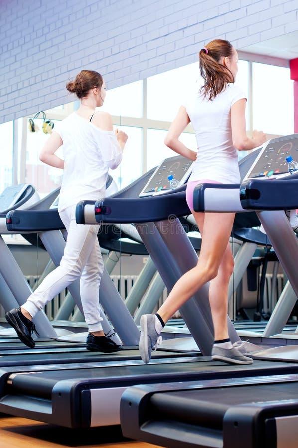 Two young sporty women run on machine stock photo
