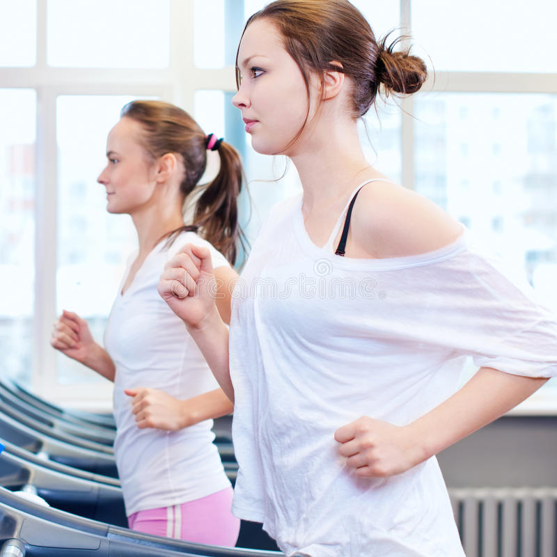 Two young sporty women run on machine stock image