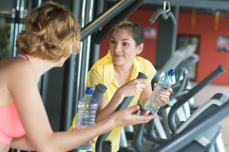 Two young sporty women run on machine in gym royalty free stock photos