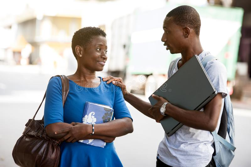 Two young students standing outdoors and discussing after school, Concept of Education. Portrait of two young students discussing outside on campus of university stock images