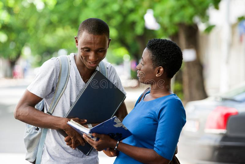 Two young students standing outdoors and discussing after school, Concept of Education. Portrait of two young students reading a book and chatting outside on stock image