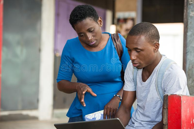 Two young students standing outdoors and discussing after school, Concept of Education. Portrait of two young students working a laptop and chatting outside on royalty free stock photo
