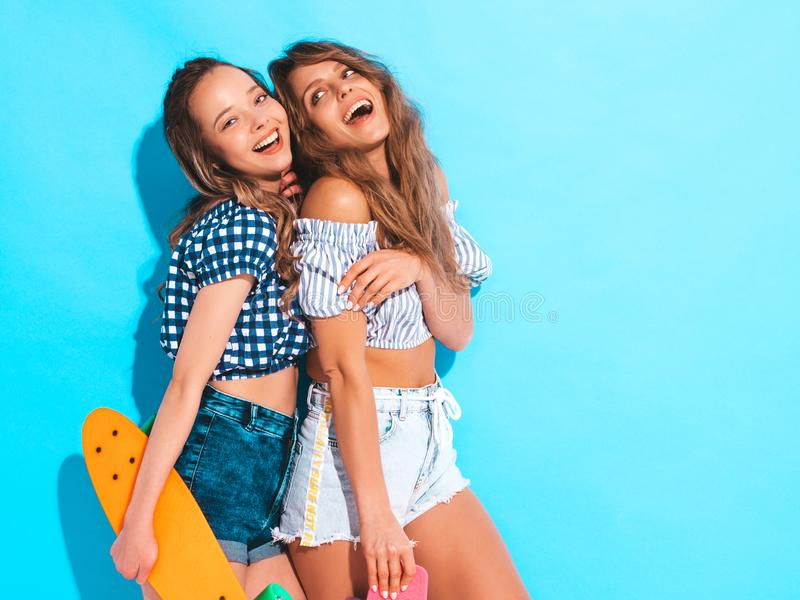 Two young stylish smiling beautiful girls with colorful penny skateboards royalty free stock photos