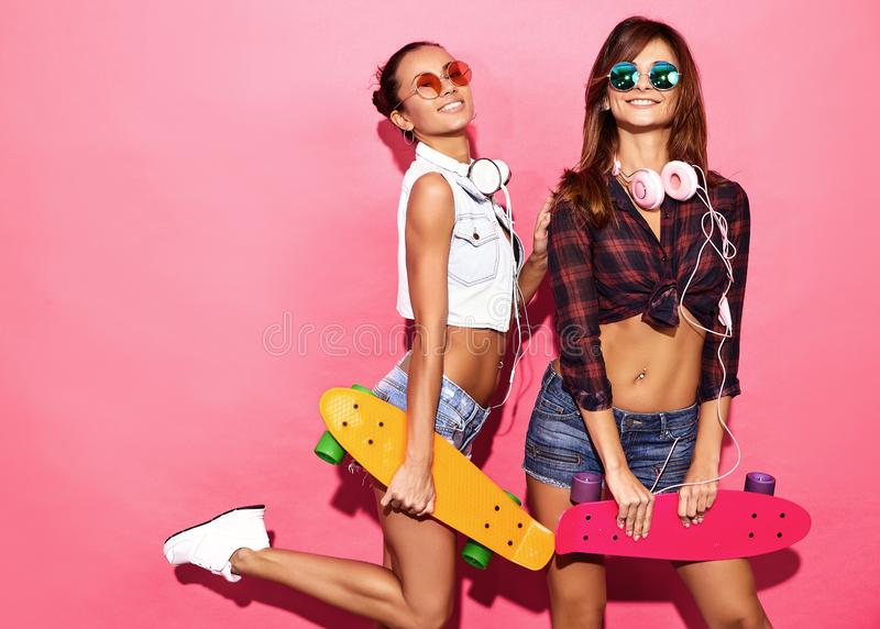 Two young stylish woman models in summer hipster clothes. Two young stylish smiling brunette women with penny skateboards. Models in summer hipster clothes royalty free stock image