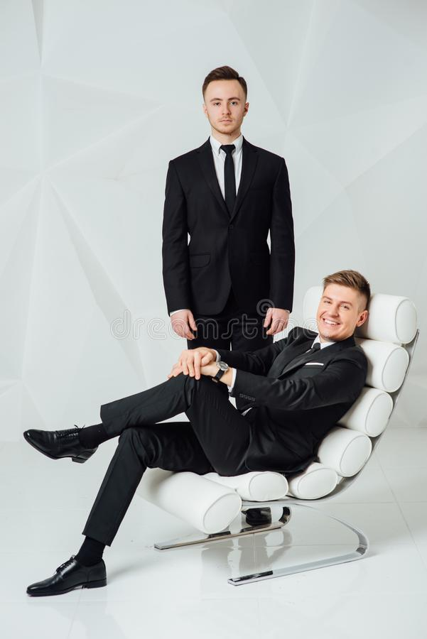 Two young successful guys in black suits royalty free stock photo