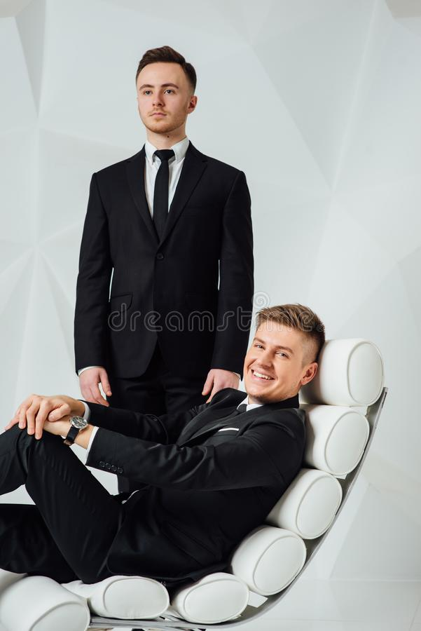 Two young successful guys in black suits royalty free stock photos