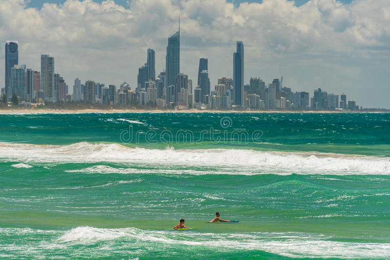 Two young surfers with Gold Coast cityscape on the background stock photos