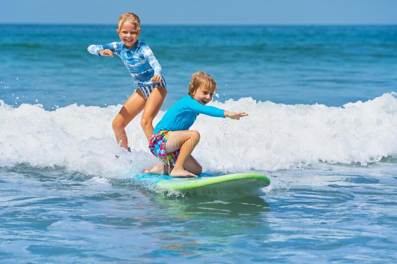 Two young surfers ride with fun on one surfboard. Happy baby boy and girl - young surfers ride with fun on one surfboard. Active family lifestyle, kids outdoor stock photography