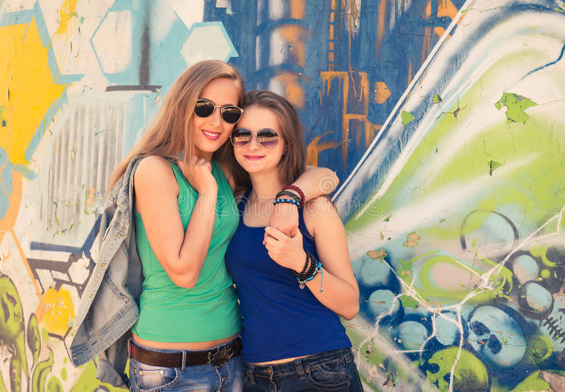 Two young teen hipster girl friends together having fun graffiti royalty free stock images