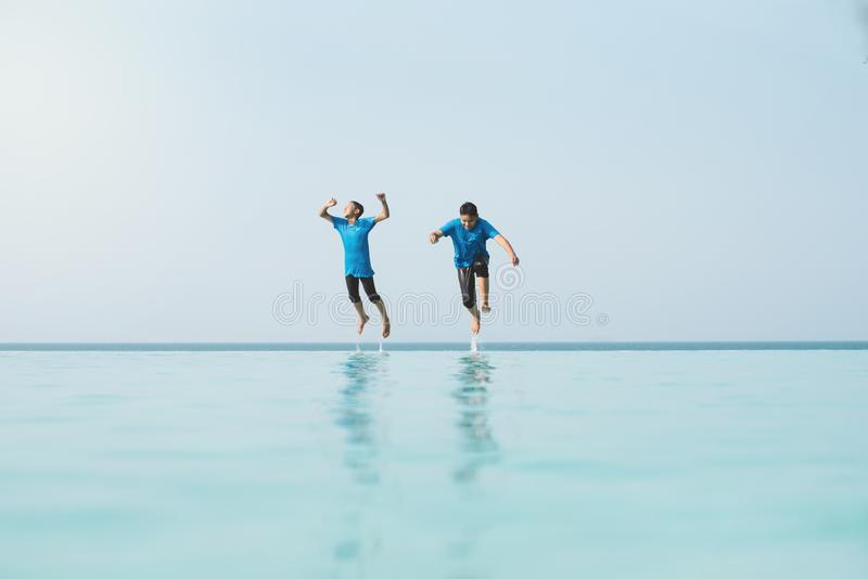 Two young teenager jumping together into a overflow swimming pool. Concept of holidays, vacation, happiness and friends having fun stock image
