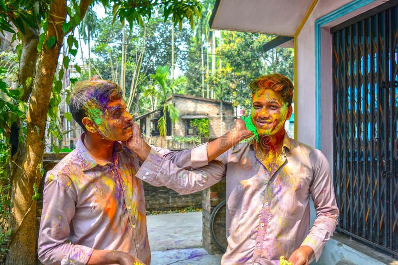 Close up portrait of two young teenagers are coloring each other during the Holi festival in India. royalty free stock photography