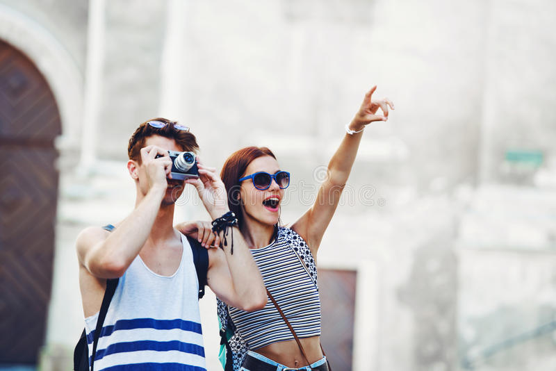 Two young tourists sightseeing a town, pointing with finger. Modern stock photography