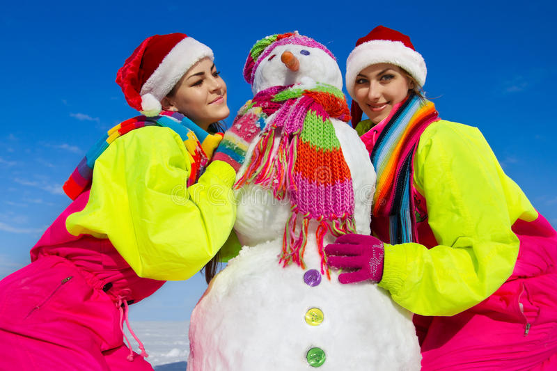 Two young woman holding a snowman royalty free stock photo
