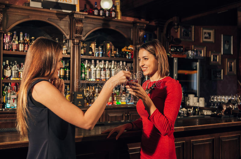 Two young woman near a bar drinking and chatting each others stock images