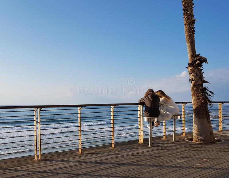 Two young woman sitting in new promenade of Bat Yam,Israel stock photography