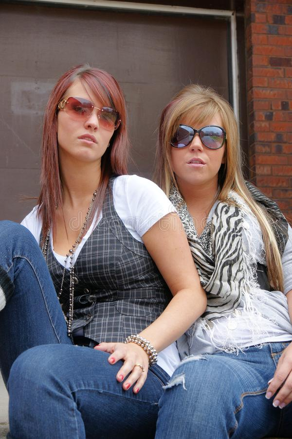 Two young woman with sunglasses on looking cool royalty free stock image