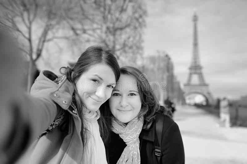 Two young woman taking a selfie near the Eiffel tower. Black and white photo of two young women taking a self portrait (selfie) near the Eiffel tower royalty free stock photography