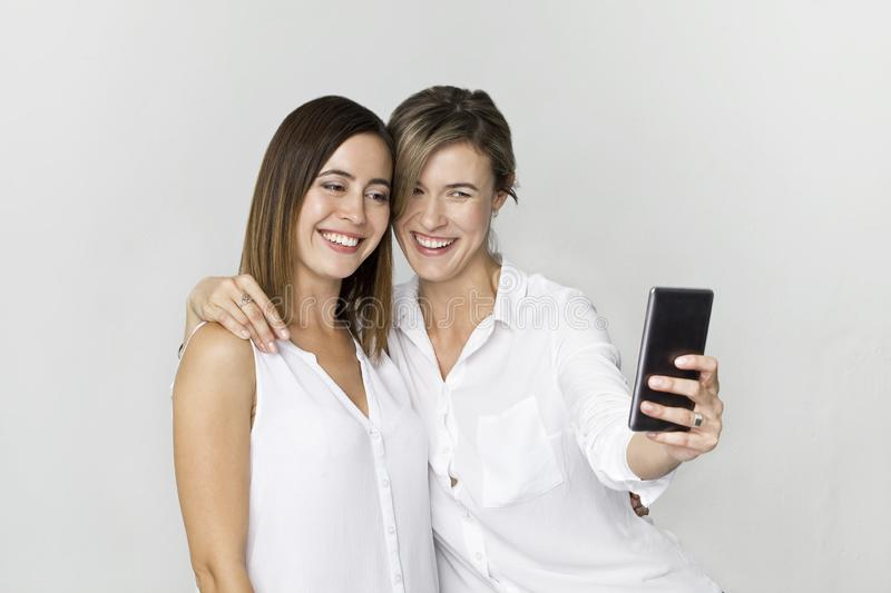 Two young woman in white shirt having fun with making selfie. St stock photography