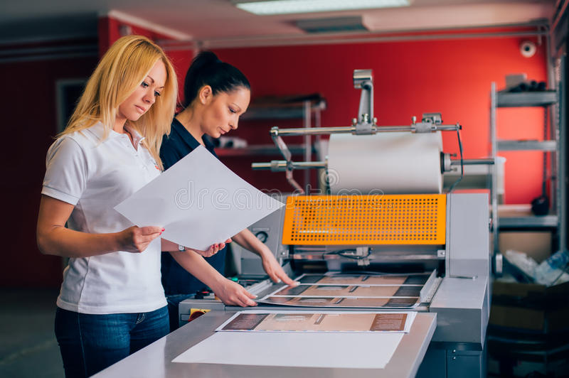 Two young woman working in printing factory royalty free stock images
