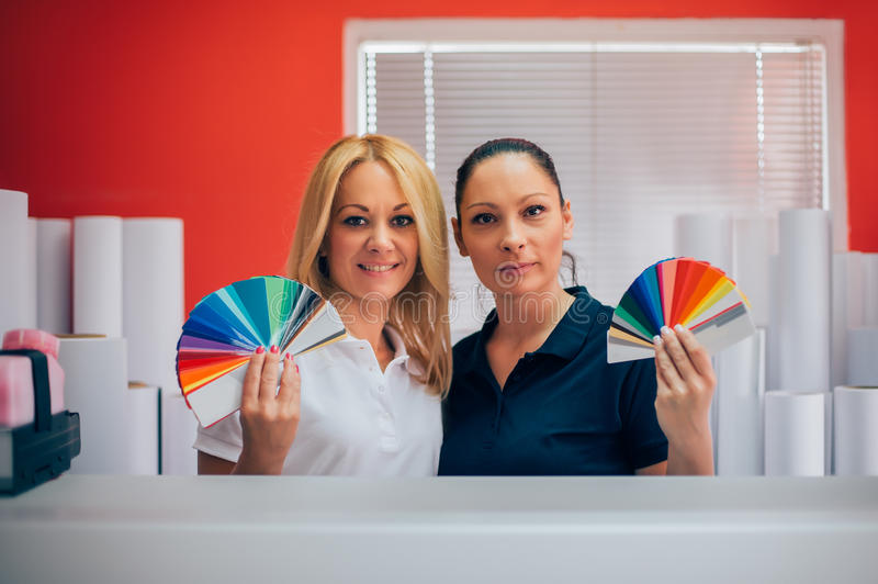 Two young woman working in printing factory stock photography