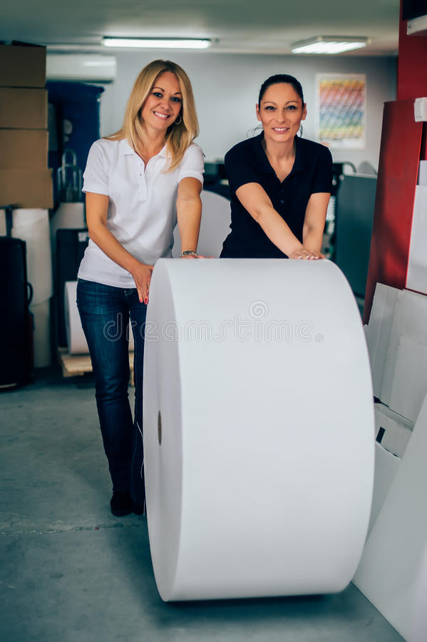 Two young woman working in printing factory stock photos
