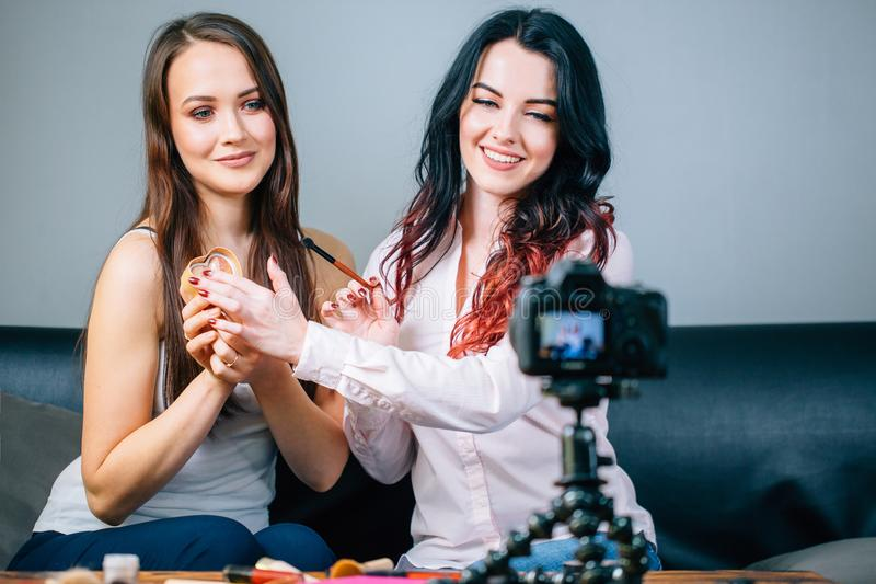 Two young womans reviewing beauty products on video blog at home royalty free stock photos