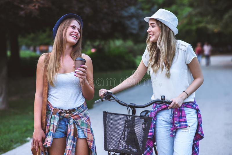 Two young women holding hands walking in green park. Best friends. Two young women best friends walking on summer day in green park royalty free stock photography