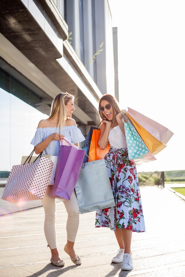 Two young women carrying shopping bags in front of a mall royalty free stock photos