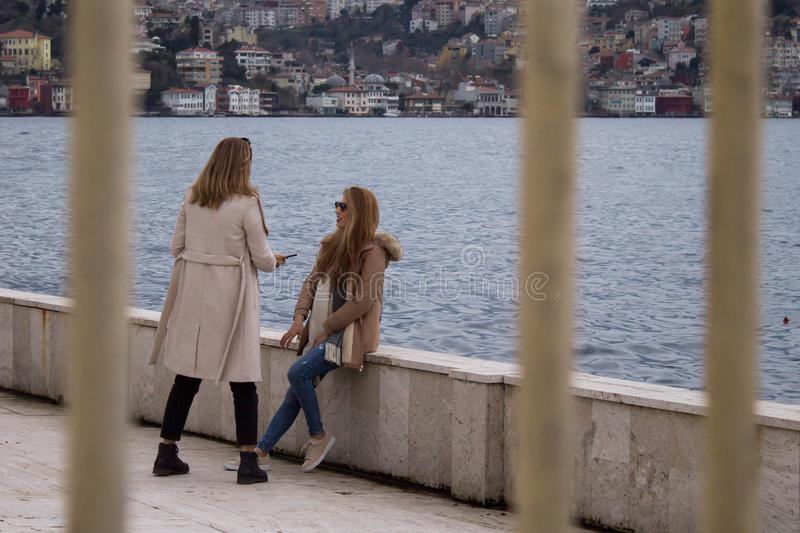 Two young women chatting near sea side. Outside behind the fence. royalty free stock images