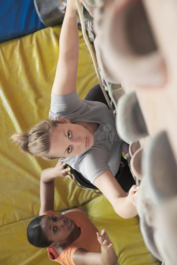 Two young women climbing in an indoor climbing gym, directly above stock photo