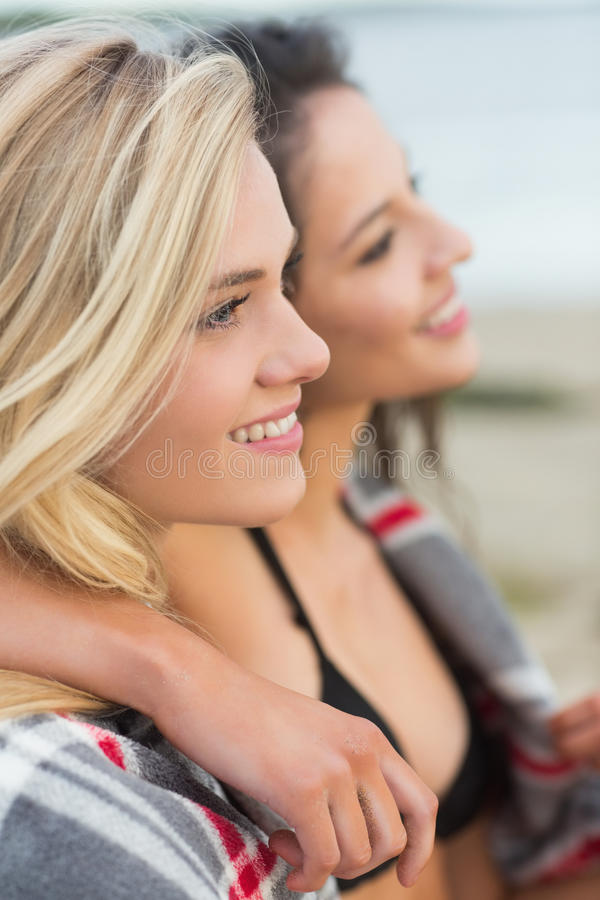 Two young women covered with blanket at beach royalty free stock photos