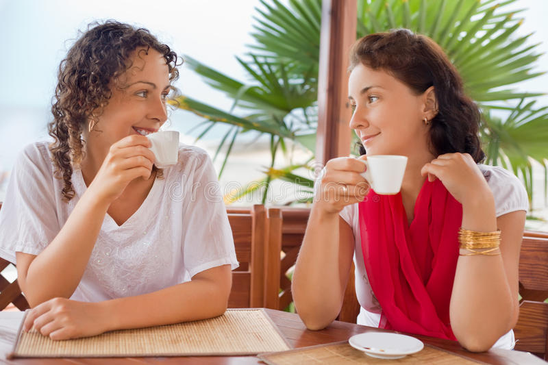 Two young women with cups sitting in an arbour stock image