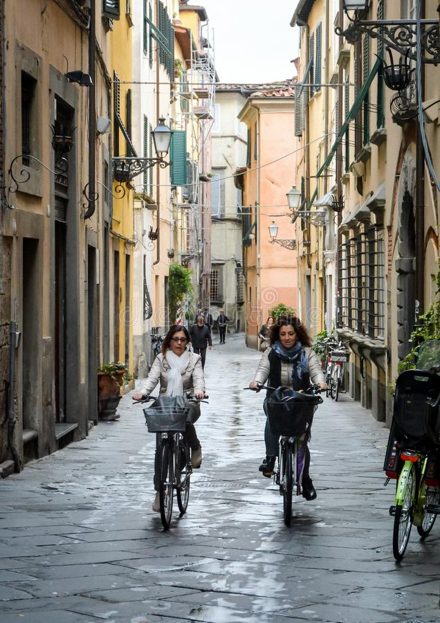Two young women cycling in Lucca, Italy royalty free stock photography